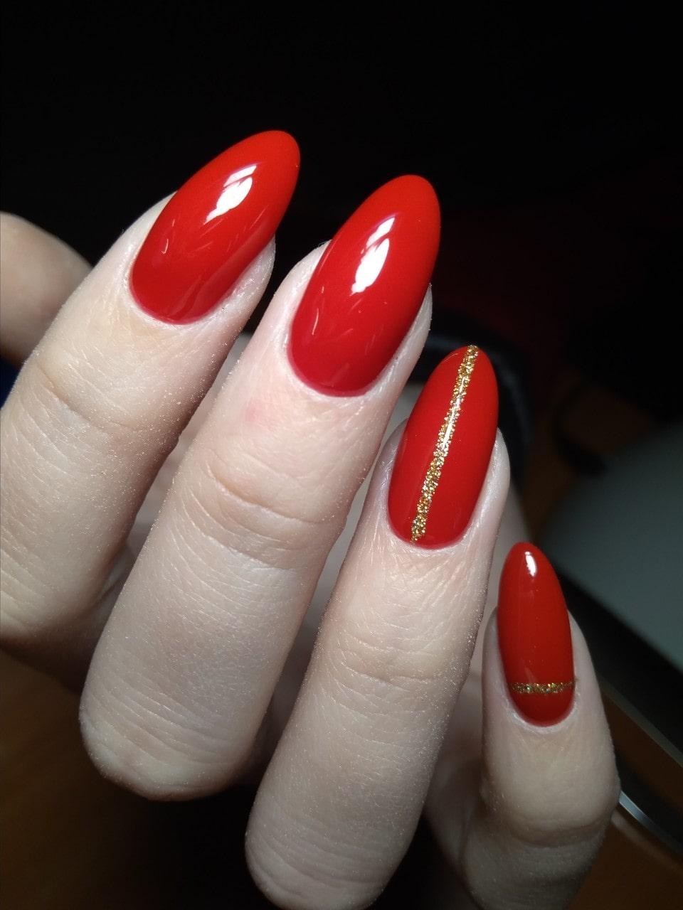 красный маникюр с золотой полоской, на миндалевидной форме ногтя