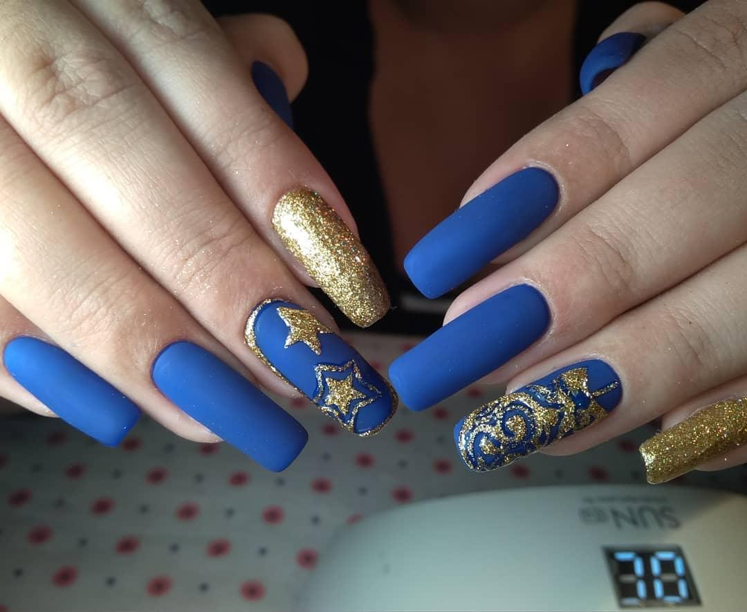 синий матовый маникюр на длинных ногтях с золотистистыми звездочками из втирки