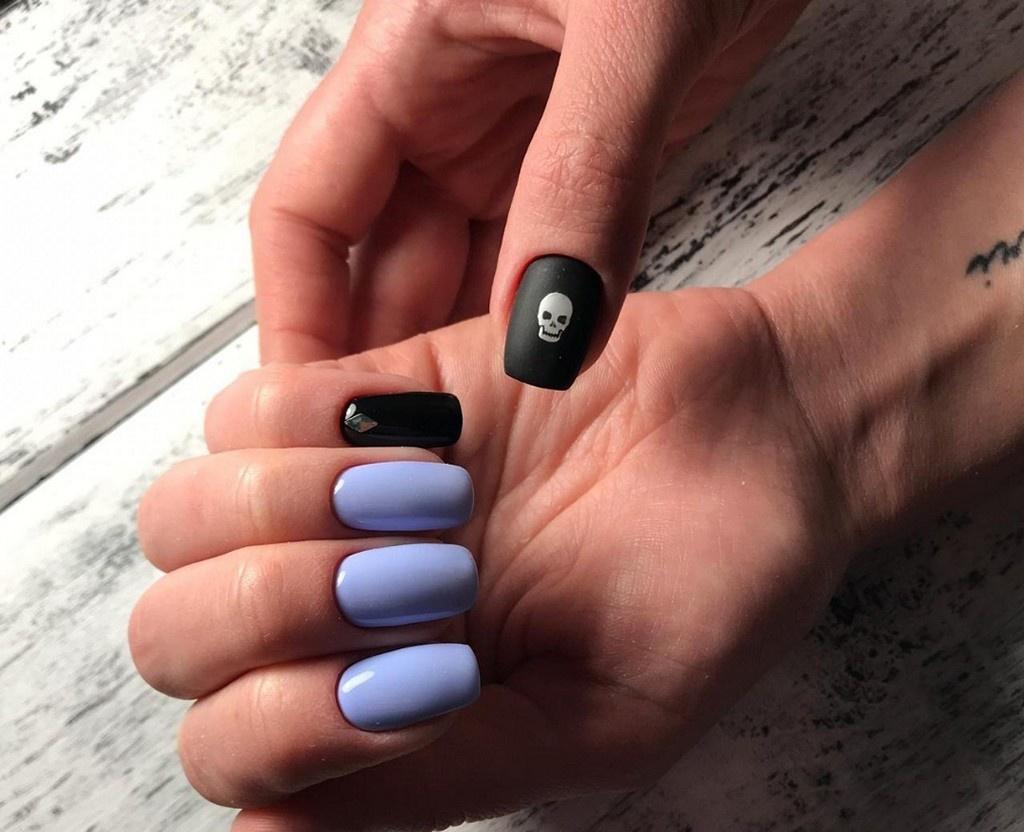 Мягкий квадрат сине-фиолетового цвета с рисунком черепа на большом пальце.