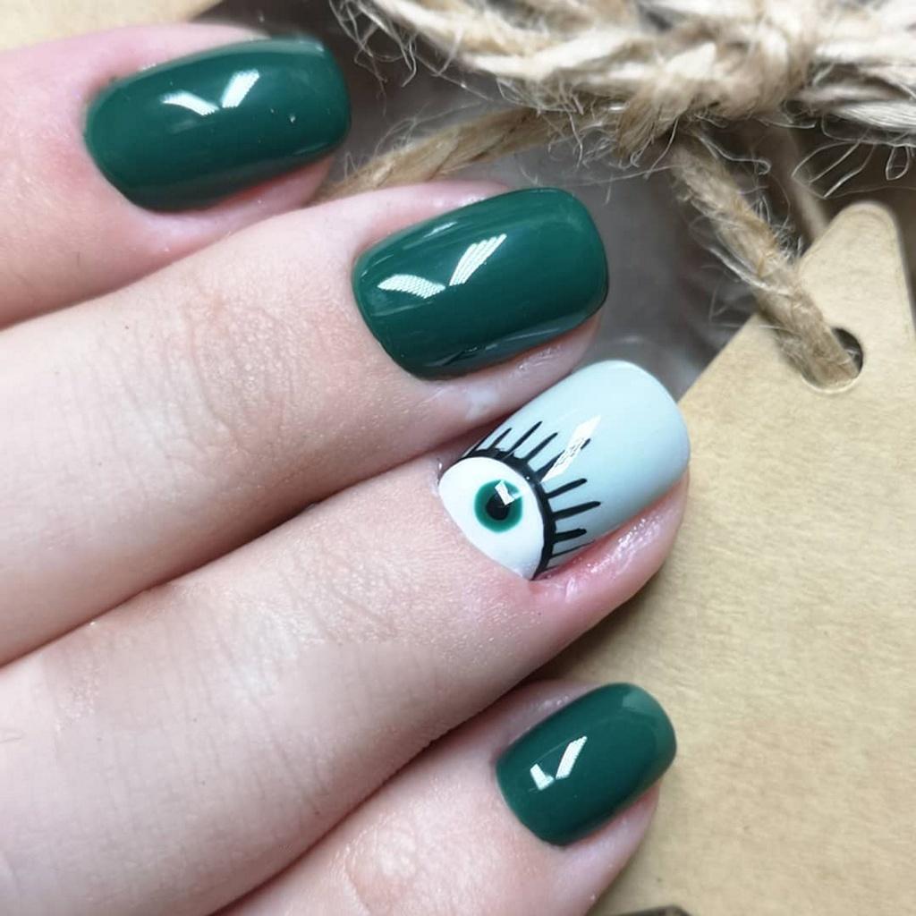Однотоный маникюр зеленого цвета с акцентом в виде нарисованого глаза на безыменямо пальце