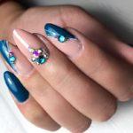 Темно синий маникюр миндалевидной формы, с негативным пространством и стразами на среднем пальце,